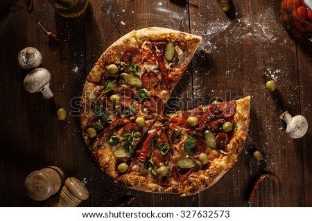 top view of fresh baked pizza without slice served on wooden table - stock photo