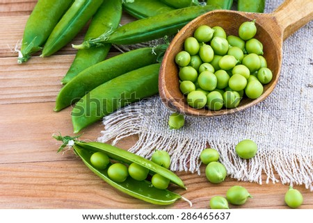 Top view of fresh green peas in a spoon on wooden background - stock photo