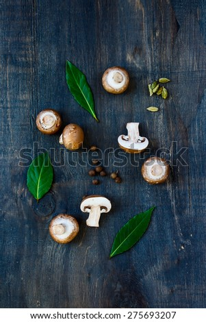 Top view of fresh mushrooms with spices and herbs on dark wooden background. - stock photo