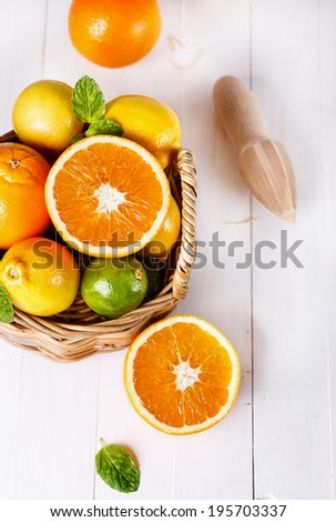Top view of fresh oranges, lemons and limes in a woven basket over white wooden background. Selective focus, shallow DoF - stock photo