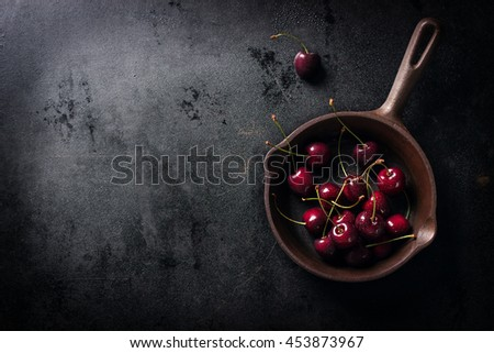 Top view of fresh red cherry on an old pan with copy space, horizontal - stock photo