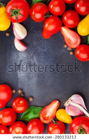 Top view of fresh ripe tomatoes with basil and garlic on a dark vintage background. Lots of copy space - stock photo
