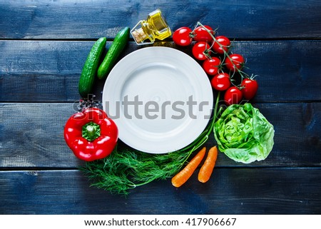 Top view of fresh vegetables for tasty vegan and diet cooking or salad making around empty plate on rustic wooden background. Vegetarian food concept. - stock photo