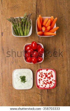 Top view of fresh vegetables in colourful bowls on wooden table. Healthy party snacks. Asparagus, cucumbers, carrots, lettuce leaves and cherry tomatoes.  - stock photo