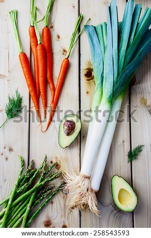 Top view of fresh vegetables on wooden background. Vegetarian food, health or cooking concept. - stock photo