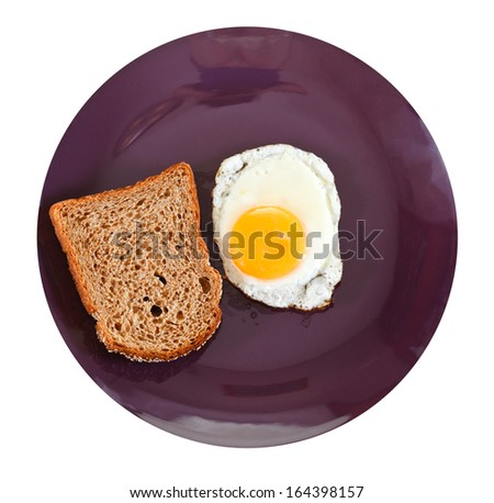 top view of fried egg and toasted rye bread on plate isolated on white background - stock photo