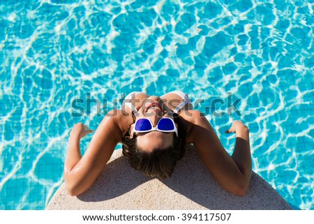 Top view of funny woman enjoying summer vacation in resort swimming pool. Beautiful brunette girl wearing sunglasses and having fun on summertime. - stock photo