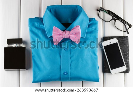 Top view of gentlemanly set: perfume, shirt, bow tie, smartphone, passport, glasses on white wooden background - stock photo
