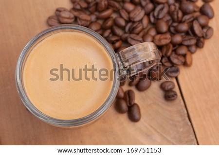 Top View of Glass Cup of Espresso Coffee on Wooden Table With Coffee Beans - Shallow Depth of Field - stock photo