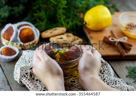 Top view of glass cup of tea with mint in female hand. Homemade chocolate chip cookies, lemon, cinnamon sticks, honey and thuja branches on wooden background - stock photo