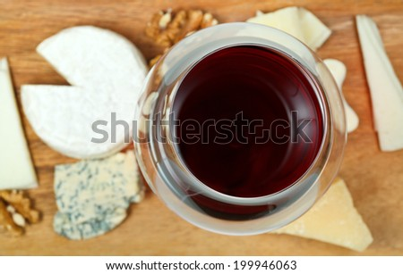 top view of glass of red wine and various cheeses on wooden plate close up - stock photo