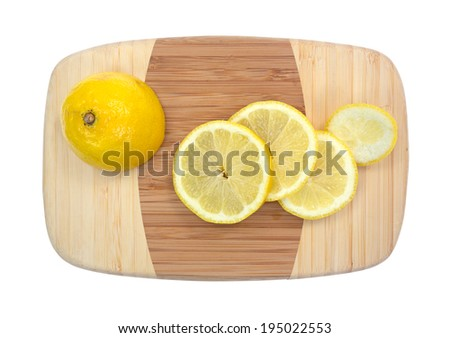 Top view of half a lemon with several slices on a small bamboo cutting board. - stock photo