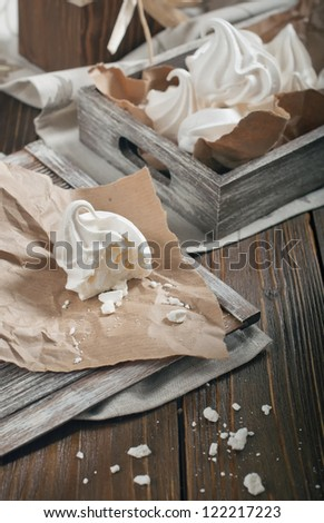 Top view of half of meringue and crumbs on paper and wooden box with meringues on dark wooden background - stock photo
