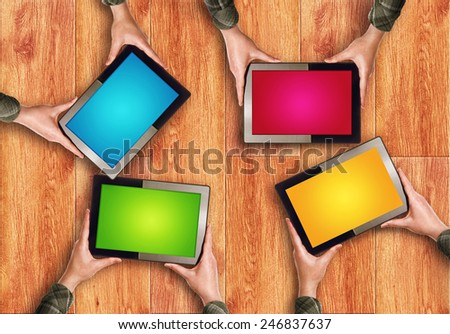 Top View of Hands Holding Four Digital Tablet Computers with Blank Colorful Screens as Copy Space over wooden background - stock photo