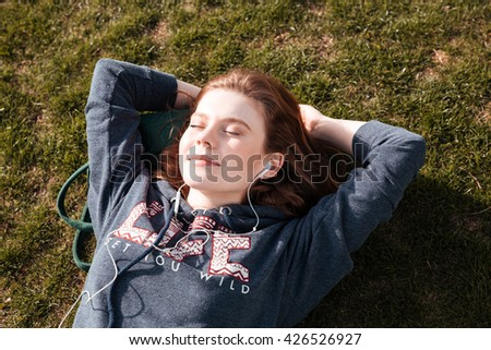 Top view of happy relaxed young woman lying on grass and listening to music - stock photo