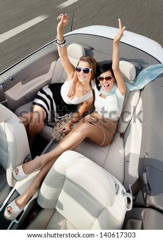 Top view of happy women in sunglasses with their hands up sit in the car - stock photo