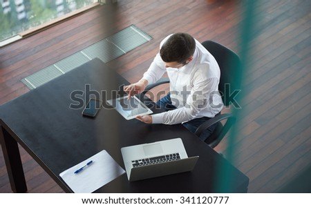 top view of happy young business man,  work tablet and laptop and relax at modern bright office interior, successful hipster with beard at workplace - stock photo