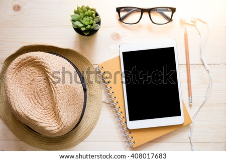 top view of hat woman glasses earphone and blank screen of tablet device over wooden table. - stock photo