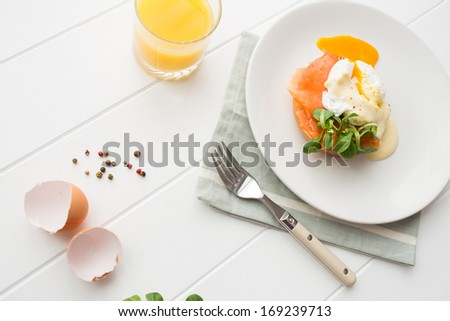 Top view of healthy breakfast with poached eggs royale (benedict), fresh orange juice and green salad on a white wooden table - stock photo