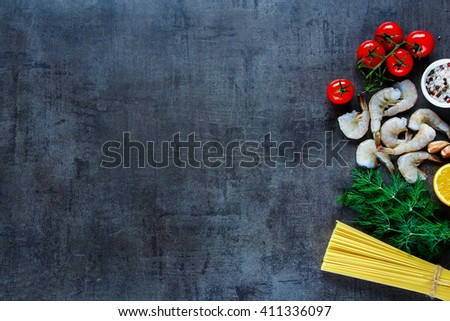 Top view of ingredients for pasta with seafood. Shrimps, spaghetti, dill, garlic, spices and cherry-tomatoes on dark grunge backdrop, place for text, border. - stock photo