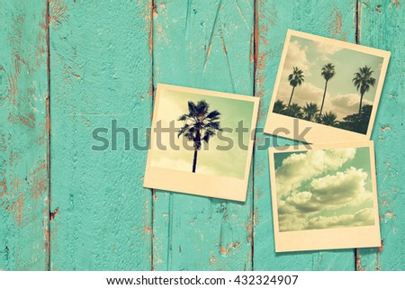 top view of instant photos album on wooden background. vintage filtered image  - stock photo