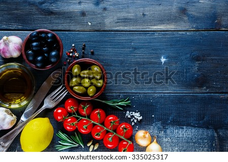 Top view of italian ingredients for cooking (tomatoe, garlic, pepper, rosemary, olives, olive oil) on dark wooden background with space for text. Vegetarian food, health or cooking concept. - stock photo
