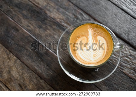 top view of latte art coffee on wooden table background - stock photo