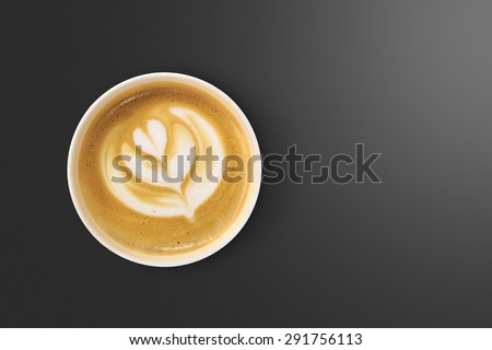 Top view of latte art coffee with heart figure, on black background. - stock photo