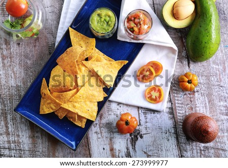 top view of light and crispy corn chips served with salsa and guacamole at blue plate with wooden table at background - stock photo