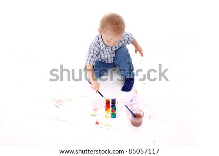 Top view of Little boy siting on floor paint - stock photo