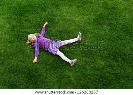 Top view of little girl lying on grass - stock photo