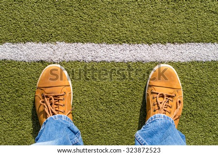 Top view of male sneakers on the artificial grass with white line - stock photo