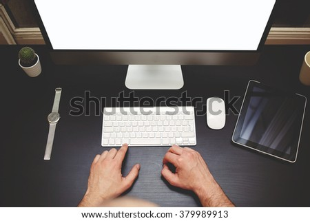 Top view of man's hands using wireless keyboard of PC with blank copy space screen for your text message or content which standing on desktop with digital tablet, computer mouse, watches, pot cactus - stock photo