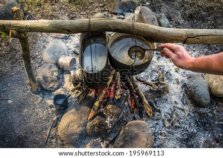 top view of man stirs ladle water that is prepared in a hike in the cauldrons, hanging over the fire - stock photo