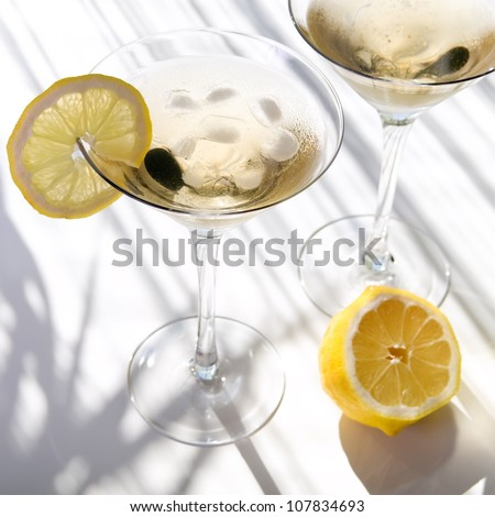Top view of martini alcohol cocktail with yellow lemon on white with shadows - stock photo
