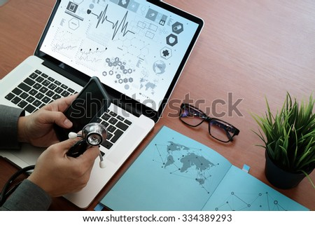 top view of Medicine doctor hand working with modern computer and smart phone with social media network on wooden desk as medical concept - stock photo
