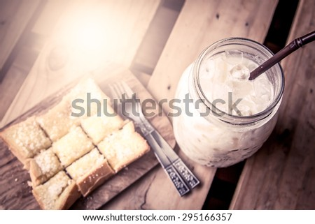 top view of milk with sweet toast on wooden table in vintage color tone - stock photo