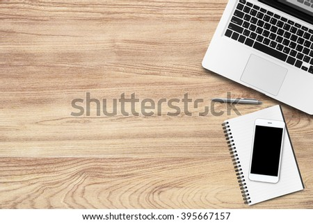 Top view of modern wood office table with laptop, smartphone, notebook and pen. Copy space is available. - stock photo