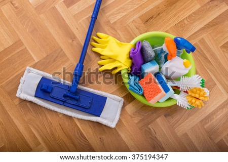 Top view of mopping stick and washbasin full of cleaning supplies and equipment on the parquet - stock photo