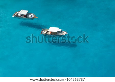 Top view of motorboats in blue, transparent waters of shipwreck bay, Zakynthos - stock photo