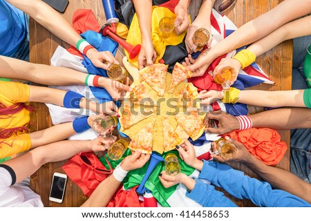 Top view of multiethnic hands of football friend supporter sharing pizza margherita - Friendship concept with soccer fan enjoying food together - People eating at party bar pub after sport match event - stock photo