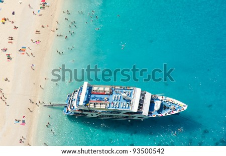 Top view of Navagio beach in Greece with cruiser anchoring next to beach - stock photo