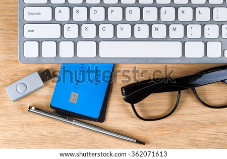 Top view of oak wood desktop with computer keyboard, credit cards, pen, reading glasses and thumb drive. Keyboard is nonfunctional generic.  - stock photo