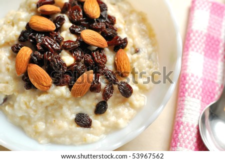Top view of oatmeal topped with raisins and nuts for a nutritious and healthy breakfast. Also for healthy lifestyle, diet and nutrition, and food and beverage concepts. - stock photo