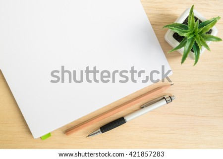 Top view of office desk table with open notebook, pencil, pen and small tree in a white pot on wood table - stock photo
