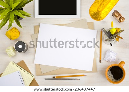 Top view of office desk with paper, stationery and tablet computer - stock photo