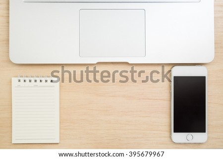 Top view of office desk with small notebook, mobile phone and laptop on wooded table - stock photo