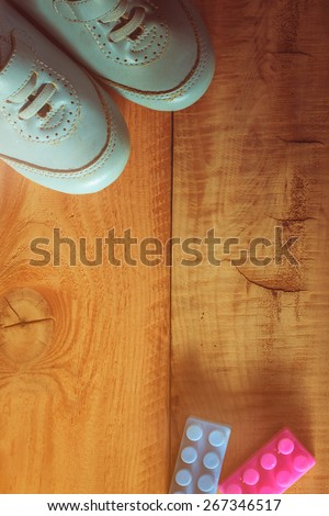 top view of old boy shoes on wooden floor with plastic toy,abstract background to first step concept.vintage color photo. - stock photo