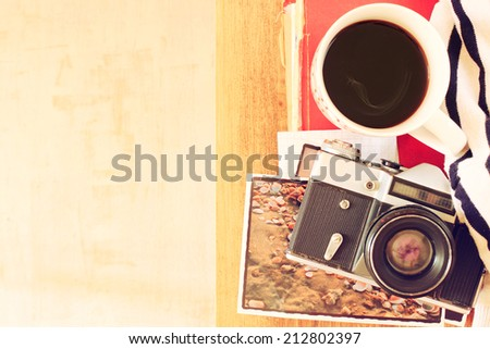 top view of old camera, cup of coffee and stack of photos. filtered image. travel or vacation concept. - stock photo
