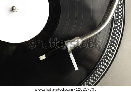 Top view of old fashioned turntable playing a track from black vinyl - stock photo